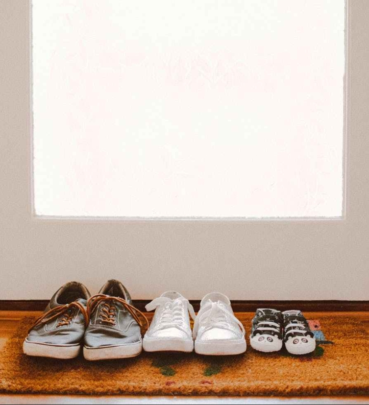 three pairs of shoes on brown rug